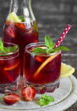 Strawberry lemonade with fresh mint and lemon in glass beakers Stock Photos