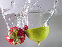 Strawberry and lime in water. Natural strawberry and lime lemon splashing in water Royalty Free Stock Photography