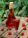 Strawberry liquor on a wooden background. Homemade strawberry liquor on a wooden background stock image