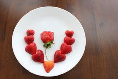 Strawberries on plate. A white plate with red ripe strawberries in a heart shape Royalty Free Stock Image