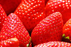 Strawberry macro. Macro view of many strawberries lying close to each others, hit by sun light Royalty Free Stock Image