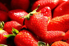 Strawberry macro. Macro view of many strawberries lying close to each others, hit by sun light Royalty Free Stock Images