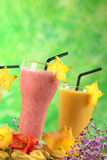 Strawberry and Mango Milkshakes. Garnished with carambola slice surrounded by flowers (Selective Focus, Focus on the front of the strawberry milkshake and the Stock Photo