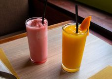 Strawberry mango shake on wooden table. Orange and pink fruit shake photo. Refreshing fruit drink. Vegetarian dessert. Strawberry and mango shake on wooden table royalty free stock photography