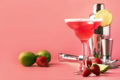 Strawberry margarita alcoholic cocktail with tequila, liqueur, berries, lime juice, sugar and ice, summer pink background, place royalty free stock photo