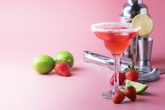 Strawberry margarita alcoholic cocktail with tequila, liqueur, berries, lime juice, sugar and ice, summer pink background, place stock image