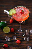 Strawberry Margarita and bartending tools,top view. From above shot of glass with ice and strawberry Margarita on counter with bartending tools and shaker Royalty Free Stock Photo