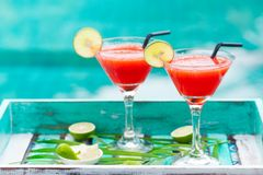 Strawberry margarita cocktail on colorful wooden background with palm leaf. Copy space Stock Photo