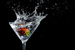 Strawberry Martini Drink Splash. Ripe red strawberry falling into a martini glass creating a splash Stock Image