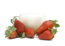 Strawberry with milk. Glass cup with milk and a strawberry. A still-life on a white background Stock Photos