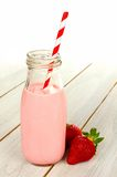 Strawberry milk in bottle on white wood Royalty Free Stock Photo