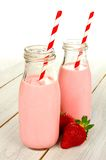 Strawberry milk in bottles on wood Stock Photography