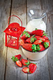 Strawberry, milk and candle lantern. Bowl with ripe strawberry, jug of milk and small candle lantern on old wood table. Selective focus Stock Photo