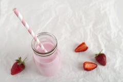 Strawberry milk in retro bottle on background horizontal. Strawberry milk bottle striped straw on crumpled paper background horizontal stock photo