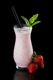 Strawberry milk shake. Isolated on a black background garnished with fresh green mint Stock Photos