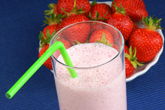 Strawberry milkshake. With green straw and some strawberries in the background over a blue tablecloth Royalty Free Stock Photos