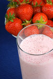 Strawberry milkshake. Close-up and some fresh strawberries in the background over a blue tablecloth Royalty Free Stock Images