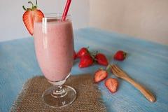Strawberry milkshake on blue wooden blackground Stock Photos