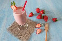 Strawberry milkshake on blue wooden blackground Royalty Free Stock Photos