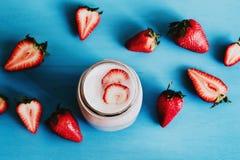 Strawberry milkshake in the glass jar blue vintage background. Batido de fresa stock photos