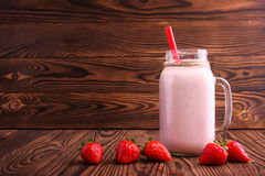 A strawberry milkshake in a mason jar. Pink smoothie on a wooden background. A yogurt with a straw and fresh berries. Copy space. Stock Images