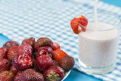 Strawberry milkshake near plate of berries Royalty Free Stock Image