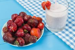 Strawberry milkshake near plate of berries Stock Photography