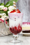 Strawberry milkshake and piece of cake in the background Stock Photo