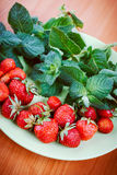 Strawberry and mint on green plate. Toned Stock Photography