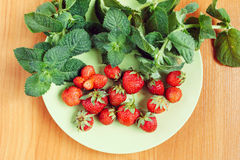 Strawberry and mint on green plate. On wooden table Royalty Free Stock Image