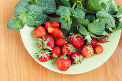 Strawberry and mint on green plate on wooden table. Slightly toned Royalty Free Stock Image