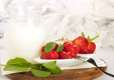 Strawberry with a mint and jug of milk Stock Photos