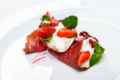 Strawberry and mint in white cream covered with sliced jamon. Royalty Free Stock Images