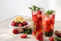 Strawberry Mojito. Cold summer mojito cocktail with strawberries, mint, lemon and ice in a glass on a bright table. summer refresh stock image