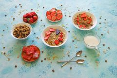 Strawberry, muesli, milk and Turkish delight on a turquoise table. Sweet delicious Breakfast stock image