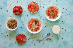 Strawberry, muesli, milk and Turkish delight on a turquoise table. Sweet delicious Breakfast stock photography