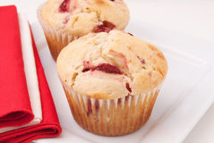 Strawberry Muffins. Homemade strawberry muffins made with buttermilk and frozen berries. Served on a square plate with red and white napkins. Selective focus and Stock Photo