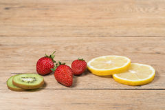 Strawberry next to lemon and kiwi fruit Stock Photos