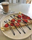 Strawberry and Nutella Crepe with Galão. Served in a restaurant in Portugal. Galão is a traditional coffee drink in Portugal stock photo