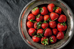 Strawberry in the old metal plate on the black stone table  top view Royalty Free Stock Photo