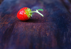 Strawberry on old wooden background. One strawberry on old wooden table background Royalty Free Stock Photography