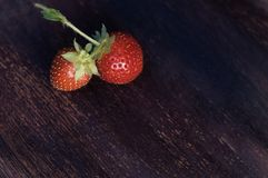 Strawberry on old wooden table. Two strawberry on old wooden background Royalty Free Stock Photos