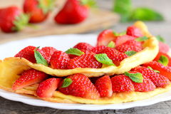 Strawberry omelette. Fried omelette filled with fresh strawberries and garnished with mint on a plate. Fresh strawberries. Recipes for kids. Healthy omelette stock photo