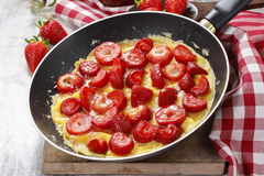 Strawberry omelette on frying pan Stock Photos