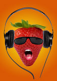 Strawberry. With open mouth and sunglasses listening to music on headphones Stock Photo