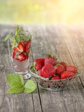 Strawberry openwork vase in the background of the glass with a strawberry drink on wooden table on a Sunny day. The Royalty Free Stock Photography