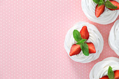 Strawberry Pavlova dessert. A small meringue Pavlova dessert with some strawberry slices garnished with mint leaves on a pink dotted background. Top view Stock Images