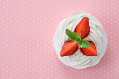 Strawberry Pavlova dessert. A small meringue Pavlova dessert with some strawberry slices garnished with mint leaves on a pink dotted background. Top view, all in Stock Images