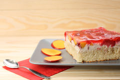 Strawberry and peach cake with gelatin on grey plate on wooden t Royalty Free Stock Photography