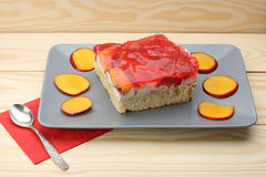 Strawberry and peach cake with gelatin on grey plate on wooden t Royalty Free Stock Photo